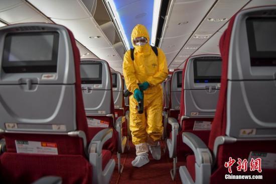 2月7日,HU7281航班抵达海口美兰国际机场,海航物业美兰机场机上清洁队工作人员立即开始登机工作。图为身着防护服的工作人员对航班客舱进行消毒作业。<a target='_blank' href='http://www.chinanews.com/'>中新社</a>记者 骆云飞 摄