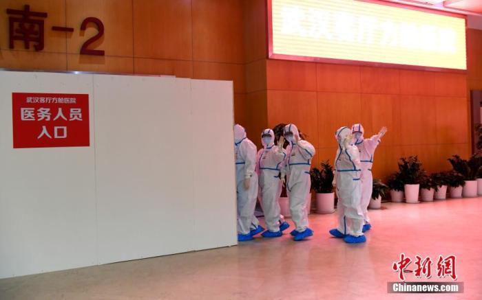 """2月7日晚,武汉客厅""""方舱医院""""开始集中收治新冠肺炎轻症病人。图为医护人员进入""""方舱医院""""诊治病人。 安源 摄"""