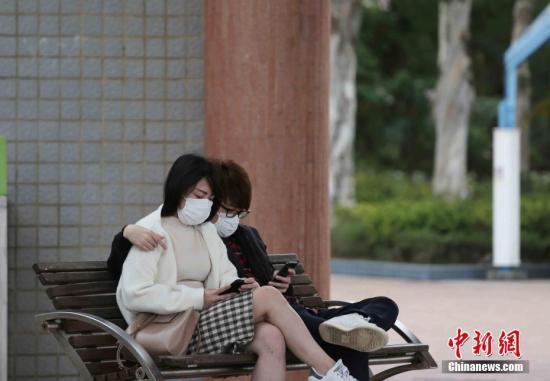 """資料圖:""""新冠疫情""""下的香港周日,戴上口罩一對情侶在公園安坐休息。 <a target='_blank' href='http://www.jylmpo.tw/'>中新社</a>記者 洪少葵 攝"""