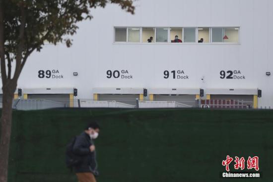 2月10日,特斯拉在上海的超级工厂正式复工复产,成为中国最早一批复工的车企之一。图为生产工间窗口佩戴口罩的员工正常工作。<a target='_blank' href='http://www.chinanews.com/'>中新社</a>记者 张亨伟 摄