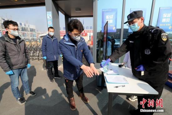 资料图:工作人员进入办公区前消毒。 中新社记者 张宇 摄
