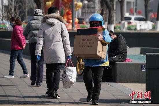 2月10日,一名外送员怀抱纸箱走出金融街购物中心。复工首日,北京金融街地区人流渐增。<a target='_blank' href='http://uean.cn/'>中新社</a>记者 崔楠 摄