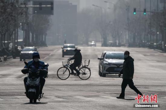 2月10日,北京民众戴口罩经过金融大街。复工首日,北京金融街地区人流渐增。/p中新社记者 崔楠 摄