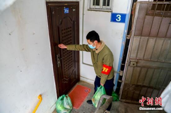 2月10日,武汉市江汉区新华街取水楼社区为辖区的老人送菜上门,社区工作人员把菜放在门口,敲门提醒老人菜已送到。 中新社记者 张畅 摄