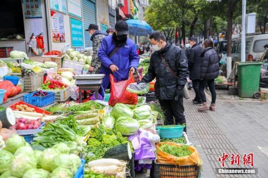 """2月10日,武汉市江汉区新华街明渠净菜市场门前的人行道上,一个简单的马路菜场业已成形,多种常见的蔬菜、水果和鸡蛋摆满摊位,于疫情之中,解决了周边居民的""""菜篮子""""问题。武汉市政府目前正在推动逐步恢复农贸市场经营,组织露天马路市场营业,截至2月8日,已有14个露天马路市场开始营业。 中新社记者 张畅 摄"""