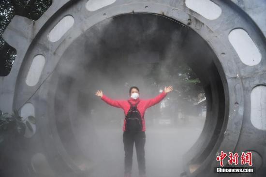 2月10日,为做好复工疫情防控工作,在位于重庆南岸区一企业大门处,企业安装了自动喷雾消毒装置,为进出企业的员工进行全身消毒杀菌。图为企业员工经过喷雾消毒处。<a target='_blank' href='http://vsfd.cn/'>中新社</a>记者 陈超 摄
