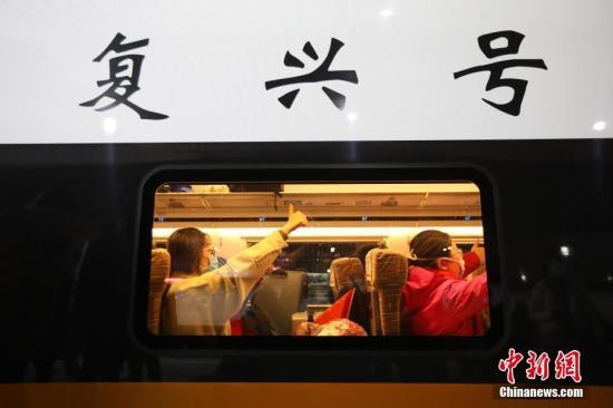 2月10日,由江苏各地中医系统43名医务工作者、江苏省卫生健康委员会派出领队组成的第三支国家中医医疗队(江苏)在南京集结,奔赴湖北省武汉市,协助当地开展医疗救治工作。图为医务工作者在车厢内为此行加油。 中新社记者 泱波 摄