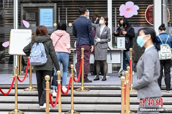 2月10日,复工首日的广州,珠江新城中央商务区一写字楼入口处设置体温检测点,工作人员为进入大楼的人员检测体温。<a target='_blank' href='http://sanli668.com/'>中新社</a>记者 陈骥旻 摄