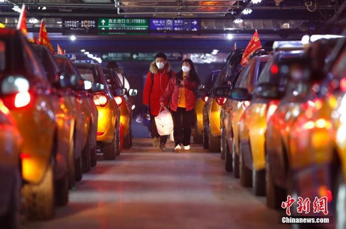 """2月9日晚,抵达北京南站的返京旅客乘坐出租车离站。2月10日北京将迎来春节假期后的开工日,从北京交通部门数据显示,""""返京潮""""明显""""削峰"""",但北京交通部门周密部署战""""疫"""",避免火车站等地出现长时间断车和乘客滞留情况,从而实现返京乘客有序、高效疏散。<a target='_blank' href='http://www.chinanews.com/'>中新社</a>记者 富田 摄"""