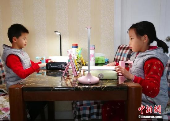 资料图:小学生们正在家中通过电脑、平板电脑等收看直播上课。/p中新社记者 翟羽佳 摄