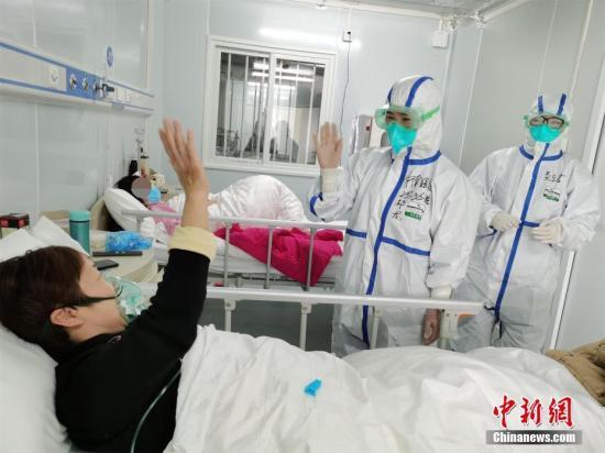 2月9日晚,武汉雷神山医院接收了第二批新冠肺炎患者,总入住患者达80余人。雷神山医院位于武汉江夏区黄家湖畔,是武汉新建的第二座集中收治新冠肺炎患者的专门医院,由武汉大学中南医院接管,于8日正式启用。图为医护人员为患者鼓劲加油。 <a target='_blank' href='http://www.chinanews.com/'>中新社</a>发 高翔 摄