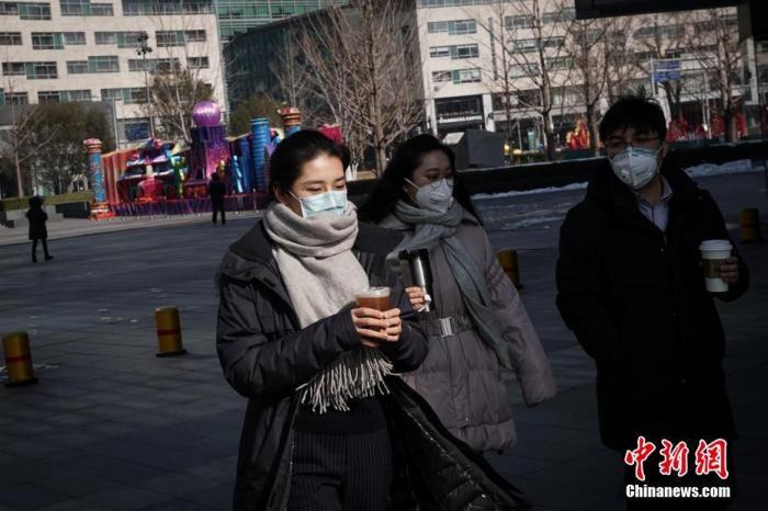 2月10日,北京民众佩戴口罩手持饮品出行。复工首日,北京金融街地区人流渐增。<a target='_blank' href='http://www.chinanews.com/'>中新社</a>记者 崔楠 摄