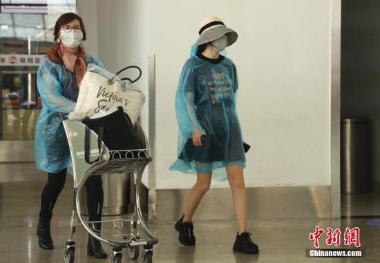 2月10日,旅客在海南三亚凤凰机场候机大厅等待登机。除了口罩以外,面具、雨衣、浴帽、太阳镜、游泳镜等,都成为出行旅客的防疫防护用品。记者 杜洋 摄