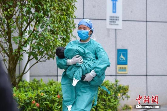 2月11日,海南省第一例新冠肺炎确诊儿童从海口市人民医院治愈出院。这也是截至目前,海南省最小的确诊病例治愈出院。入院时该患儿仅3个多月大,孩子的父母均为确诊病例。图为护士将治愈出院的女婴抱出隔离区。中新社记者 骆云飞 摄