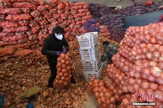 资料图:商贩整理待售蔬菜。中新社记者 武俊杰 摄