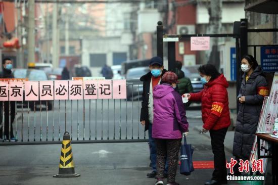 2月12日,北京丰台区北大地西区社区门口,市民在进入小区时测量体温。中新社记者 盛佳鹏 摄