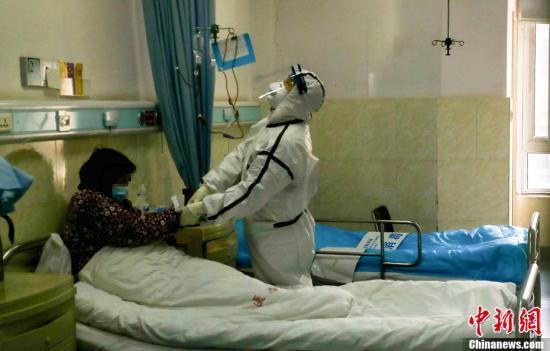 武警湖北省总队医院隔离病房内,一名医务人员在为患者打针。中新社记者 张畅 摄