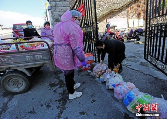 资料图:湖北武汉,超市员工把居民预定的货物放在小区门口。 李风 摄