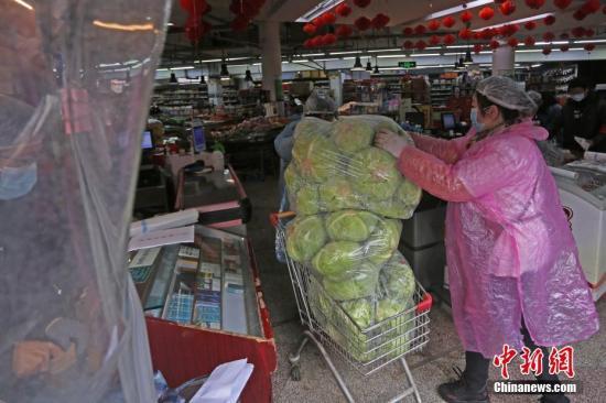 女工将需要配送的货物搬运到超市。 李风 摄
