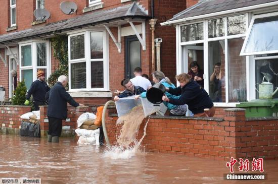 """当地时间2月17日,在风暴""""丹尼斯""""过后,英格兰西部怀伊罗斯河决堤,人们从被淹的房屋中救出水。"""