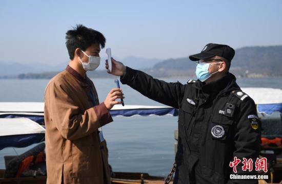 2月20日,杭州西湖水域逐步恢复船舶经营,西湖游船机动船部分开放,每船乘客量不超过载客量的50%,游客分散入座。图为西湖景区工作人员在测量船工体温。中新社记者 王刚 摄