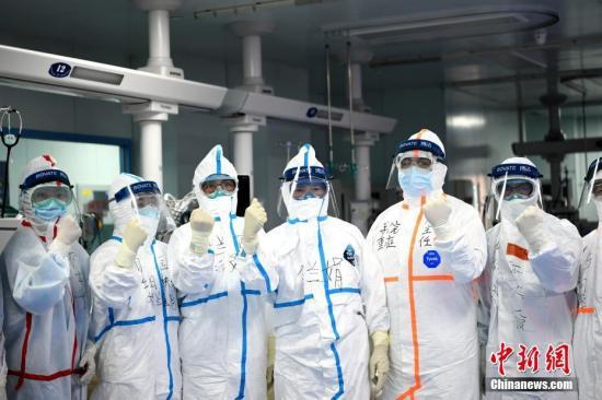 图为李兰娟院士(左四)和团队成员在进入病房前加油鼓劲。中新社记者 安源 摄