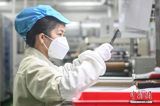 2月20日,位于广州南沙区的安捷利(番禺)电子实业有限公司内,复工人员戴着口罩在生产车间有序工作。中新社记者 陈骥�F 摄