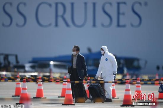"""1月20日,""""钻石公主""""号邮轮从日本横滨出发,后因船上出现新冠肺炎疫情被迫中断行程,于2月3日返回横滨港。2月5日,日本厚生劳动省宣布,邮轮上所有人员需在海上隔离14天。截至当地时间2月18日晚上11点,日本国内累计确诊新冠肺炎患者616例,其中,""""钻石公主""""号邮轮上已经有确诊的新冠肺炎病例共计542例。图为当地时间2月19日,""""钻石公主""""号邮轮滞留乘客正式开始下船。"""