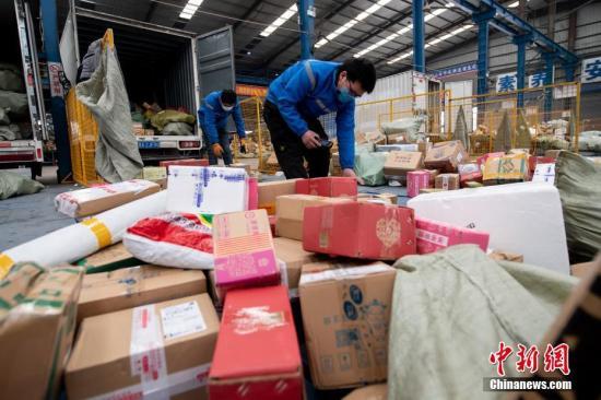 资料图:2月20日,山西省太原市中通快递山西转运中心,员工戴着口罩分拣包裹。记者 韦亮 摄