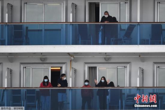 """據日本放送協會(NHK)在現場觀察到的情況,目前,已經有雙手持行李箱等大件行李的乘客走出船艙,同時,橫濱港的碼頭上已經停了十多輛巴士,這些巴士將搭載下船乘客赴主要的車站等地。厚勞省表示,下船乘客將在各自家中正常生活,不過,厚勞省會通過電話,在數日內對這些乘客的身體狀況進行確認。圖為當地時間2月19日,""""鉆石公主""""號郵輪滯留乘客正式開始下船。"""