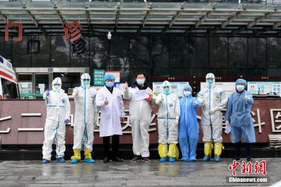 原料图:2月21日,武汉别名新冠肺热患者治愈出院。图为出院患者与医务人员相符影留念。中新社记者 安源 摄