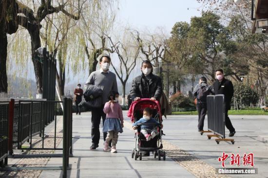 2月22日,游客戴口罩在西湖边散步。中新社记者 王伟臣 摄