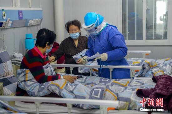 武汉火神山医院感染二科一病区的隔离病房内护士长胡晶为患者进行身体检查。中新社记者 张畅 摄