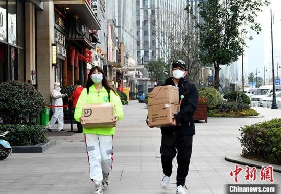 图为2月22日,杨倩(左)与田曦在搬运物资。 中新社记者 安源 摄