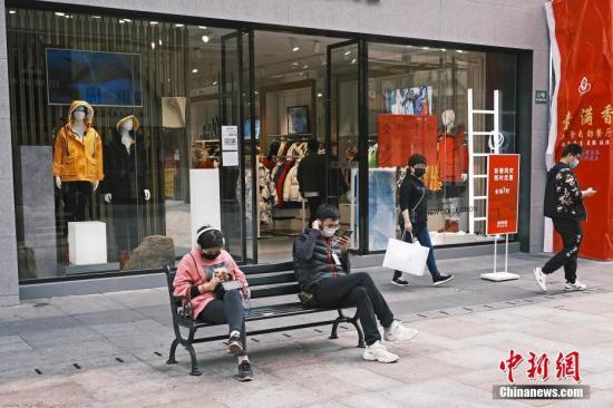 2月25日,在新冠肺炎疫情防控期间,上海市部分企业陆续复工、商铺复市。在上海江桥万达广场,民众戴着口罩在商铺购物。中新社记者 殷立勤 摄