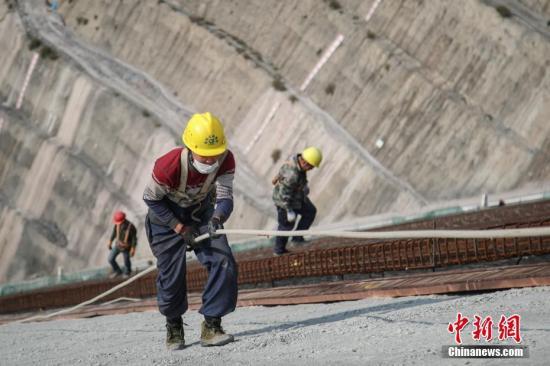 2月25日,工人正在施工。近日,坝址位于贵州省毕节市纳雍县的夹岩水利枢纽工程项目在做好疫情防控的同时有序复工,截至目前,项目复工工作面77个,占总工作面的32.6%。据悉,该工程是贵州省目前在建规模最大水利枢纽工程,大坝高154米、长429米,水库正常蓄水位高程1323米,总库容13.23亿立方米。 中新社记者 瞿宏伦 摄