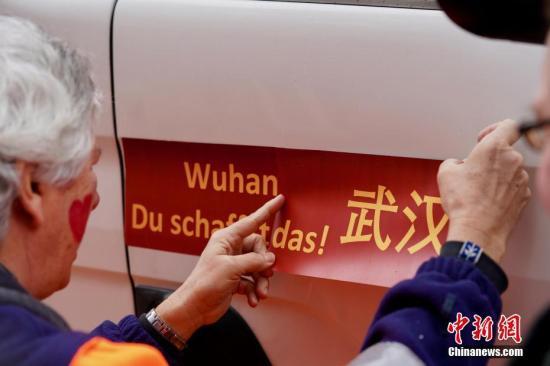 """当地时间2月24日下午,德国明斯特狂欢节最热闹的""""玫瑰星期一""""上,打头阵的""""一号""""游行花车两侧贴上了醒目的中德文""""武汉必胜""""标语,为中国、为武汉加油。"""