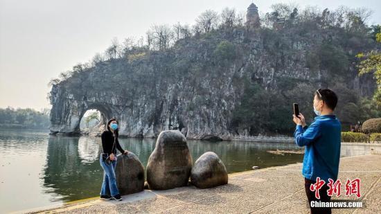 2月26日,广西桂林市象山景区正式对外恢复开放。这是广西桂林市21日宣布该市82个A级旅游景区向国内外疫情防控低风险地区游客有序开放的首个景区。图为来自广东的游客在象鼻山前拍照留念。 <a target='_blank' href='http://www.chinanews.com/'>中新社</a>记者 欧惠兰 摄