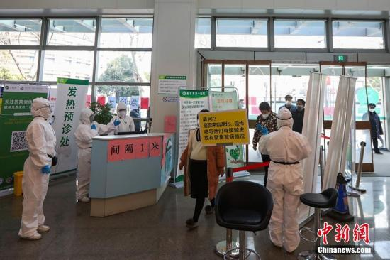 """2月27日一大早,南京市第一医院的医护人员江冰麻利地穿上防护服,戴上护目镜和医用手套,举着""""停""""和""""过""""的牌子,走到门诊大厅设立的专用通道,开始了一天的工作。 泱波 摄"""