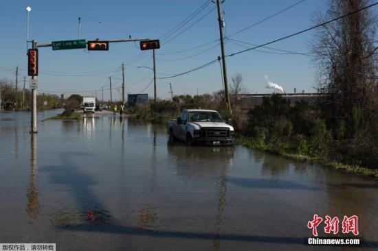 当地时间2月27日,美国休斯敦城东区的地下水管主管道破裂,导致水溢出漫延到公路上。图为救援人员封锁道路并对被困车辆人员实施救助。