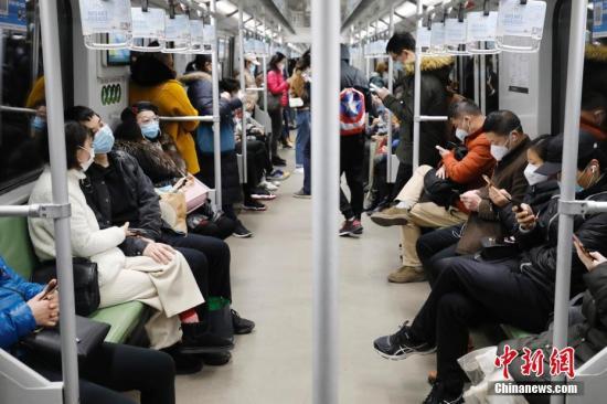 资料图:2月28日,乘客戴着口罩乘坐上海地铁出行。 中新社记者 殷立勤 摄