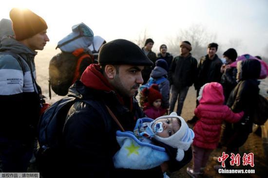 """3月1日,一位怀抱着孩子的难民正在前往土耳其与希腊边境。 土耳其政府2月27日宣布,不再阻止难民进入欧洲。大批难民和移民闻讯后连夜从土耳其向希腊边境方向涌去,经由土耳其进入希腊的""""东地中海线路""""是难民进入欧洲的主要通道。"""