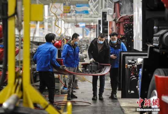 3月3日,位于新疆乌鲁木齐市经济技术开发区(头屯河区)的陕汽新疆汽车有限公司组装车间,工作人员正在加紧生产。据介绍,该企业已于2月末复工复产,目前有95名员工在岗,日产能达到15辆重型卡车。企业每周为员工发放两次口罩,每日监测员工体温,厂区每日消毒达4次,并摆放消毒液和洗手液以便员工随时消毒。 中新社记者 刘新 摄