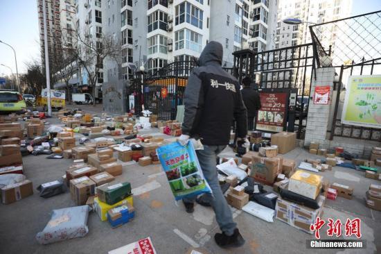 """资料图:3月3日,北京朝阳区一小区门口,快递员为居民查找搬运快递物品。受疫情影响,许多市民""""宅""""在家中,网购成为消费主流,而线上下单量也随之呈现爆发式增长,不少小区门口出现快递物品扎堆的现象。<a target='_blank' href='http://www.chinanews.com/'>中新社</a>记者 赵隽 摄"""