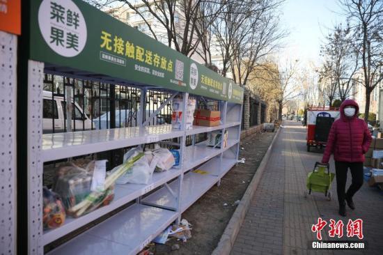 """3月3日,北京朝阳区一小区门口,居民从无接触配送存放点走过。受疫情影响,许多小区搭建起了""""社区无接触配送存放点"""",保障快递存取安全,减少人员接触,提高服务质量,坚决守好寄递安全。记者 赵隽 摄"""