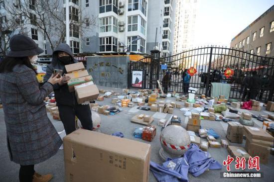 资料图:3月3日,北京朝阳区一小区门口,快递员为居民查找快递物品。记者 赵隽 摄