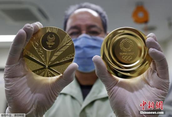 当地时间3月4日,日本大阪,一名工人展示了日本造币厂制作的2020年东京奥运会和残奥会金牌。据报道,随着举办日期的临近,2020年东京奥运会和残奥会的奖牌制作也迎来了最后阶段。