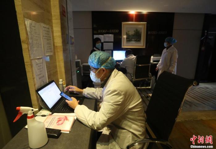 医务人员坐在电梯旁的办公桌上工作。 李风 摄