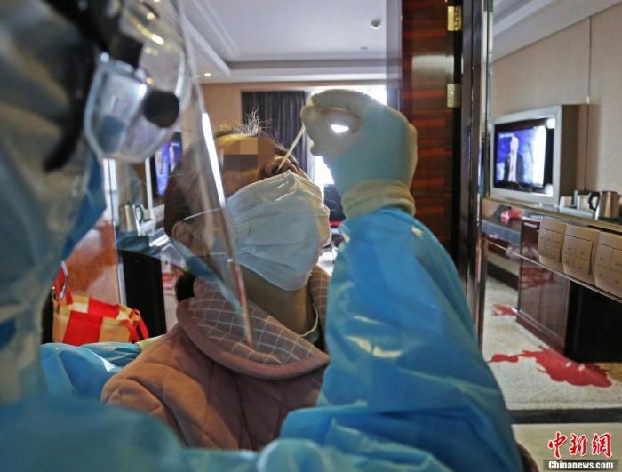 医务人员进行鼻咽拭子采样 。李风 摄