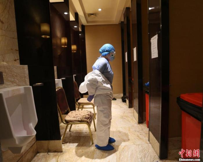 医务人员在厕所改建的消毒区进行全身消毒。 李风 摄